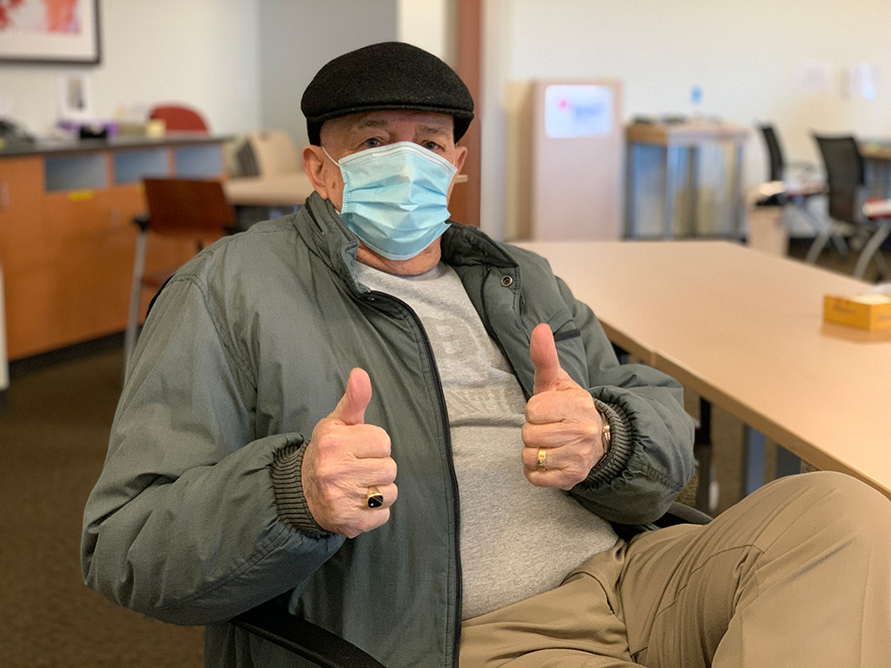 elderly man wearing mask and winter jacket gives two thumbs up