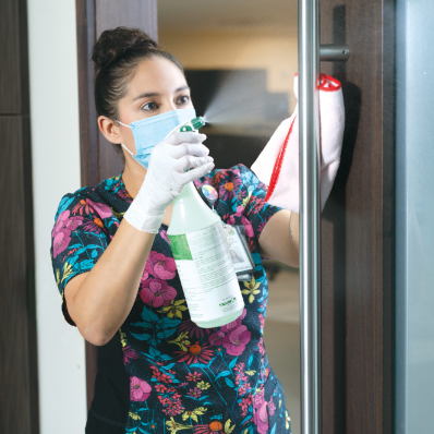 masked and gloved employee sprays disinfectant on glass and surfaces inside medical facility