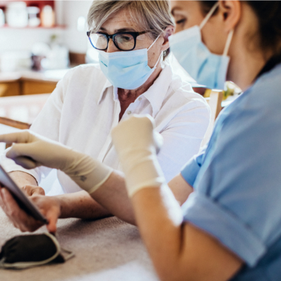 two masked females look at a digital device inside medical facility