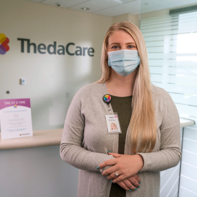 female employee wearing a mask standing in front of ThedaCare sign