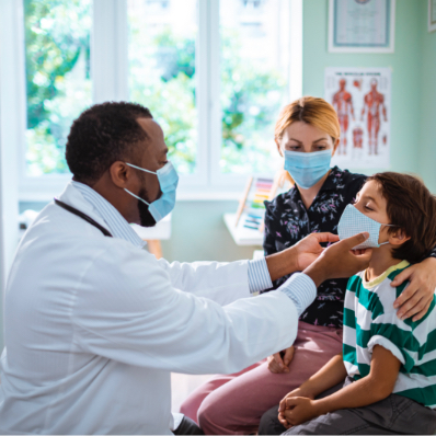 doctor wearing mask checks throat of young patient also wearing mask and sitting next to masked female parent or guardian